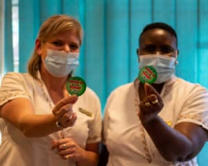 Image of our senior management with their Covid-19 vaccination badges
